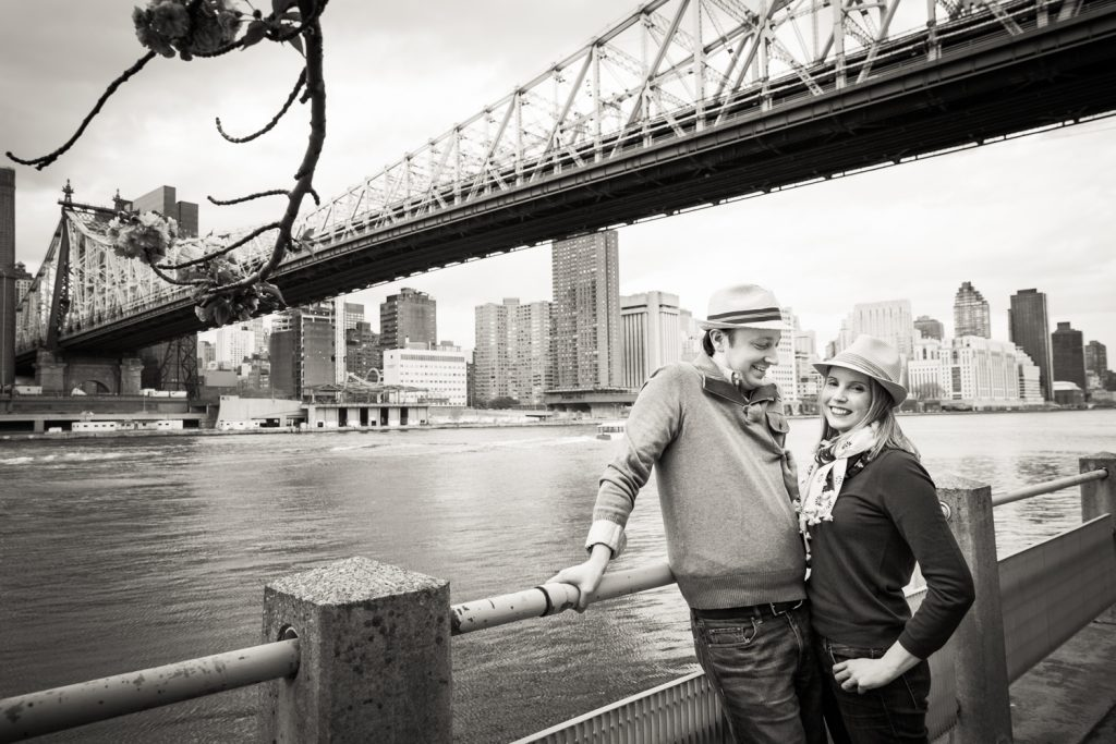 Black and white photo of couple against railing with Roosevelt Island tram in background