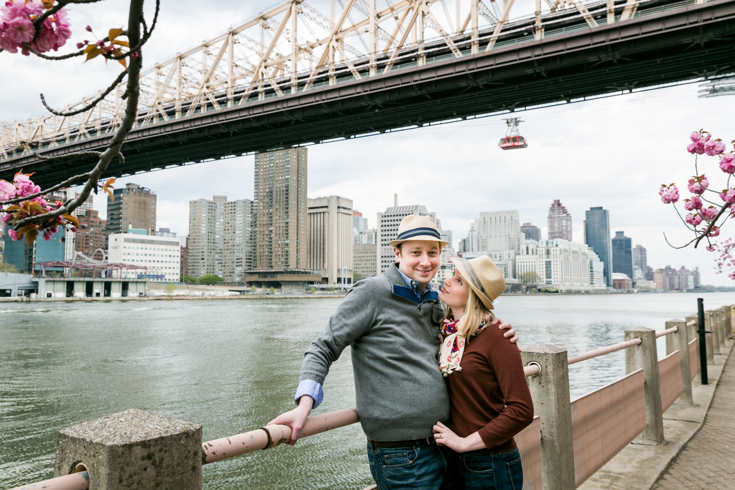 Couple against railing with Roosevelt Island tram in background