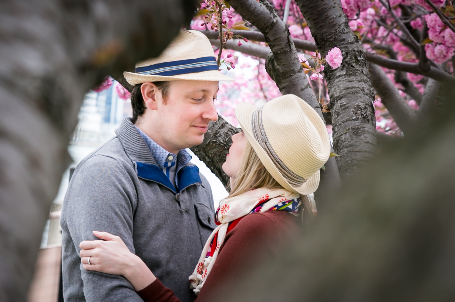 View through branches of couple hugging