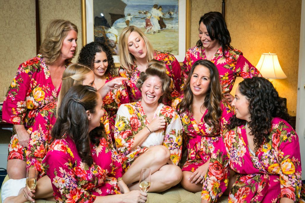 Bride and bridesmaids wearing floral robes and laughing before a University Club wedding