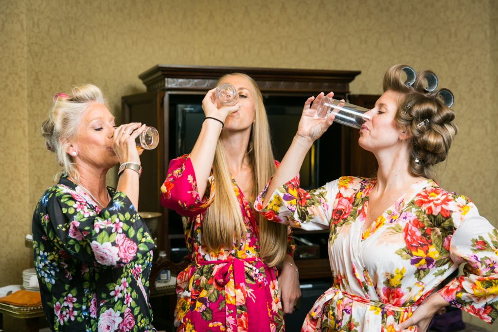 Bride, mother, and sister drinking before a University Club wedding