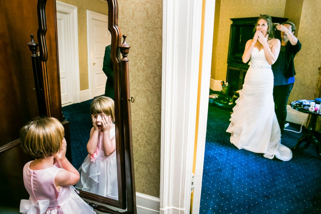 Bride getting ready and flower girl touching face in other room