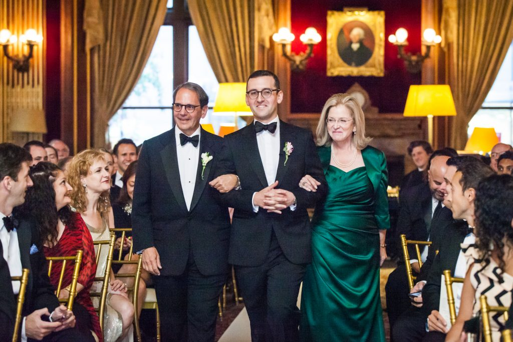 Groom and both parents walking down the aisle at a University Club wedding