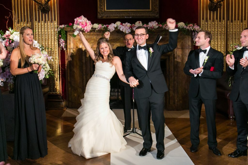 Bride and groom cheering after getting married at a University Club wedding