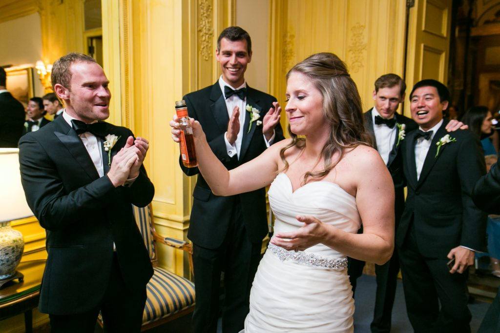 Bride taking a drink of whiskey after a University Club wedding