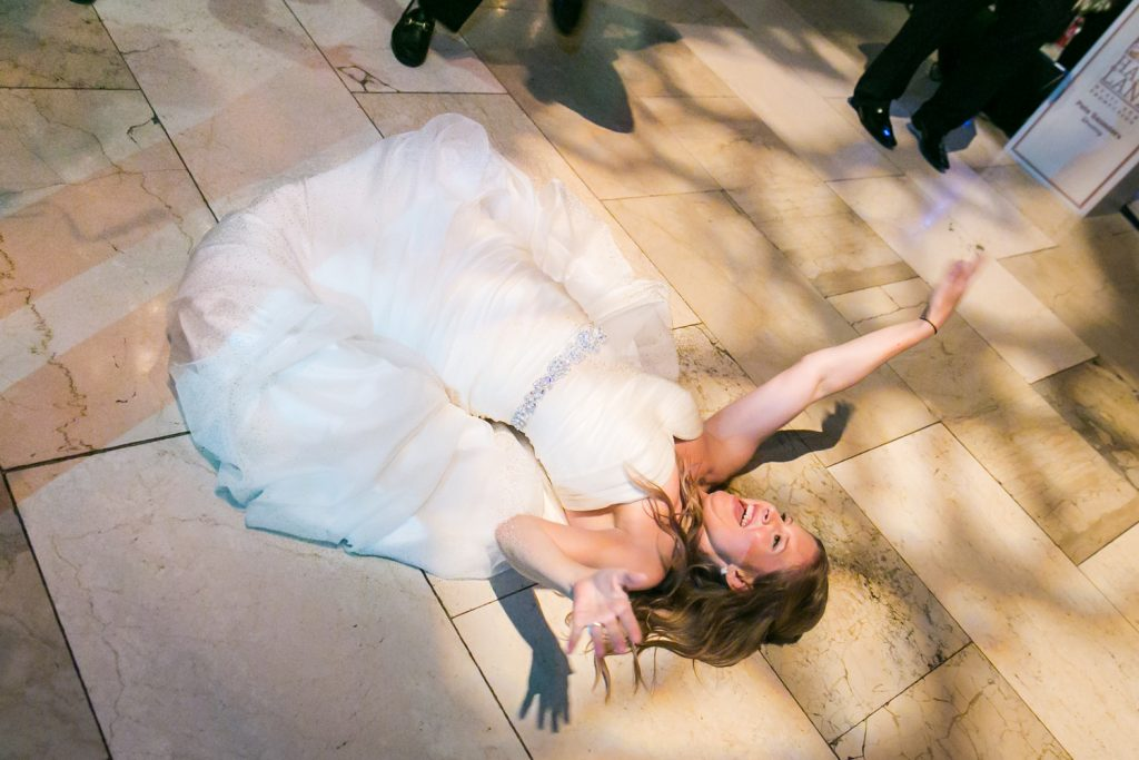 Bride laying on the dance floor at a University Club wedding