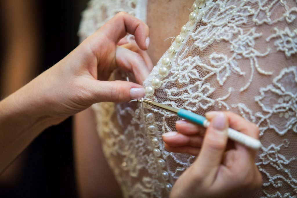 Hands using crochet hook from photographer emergency bag to close buttons on wedding dress
