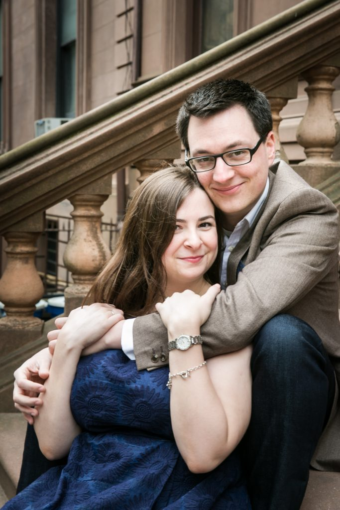Brooklyn Promenade engagement photos of couple hugging on steps of brownstone
