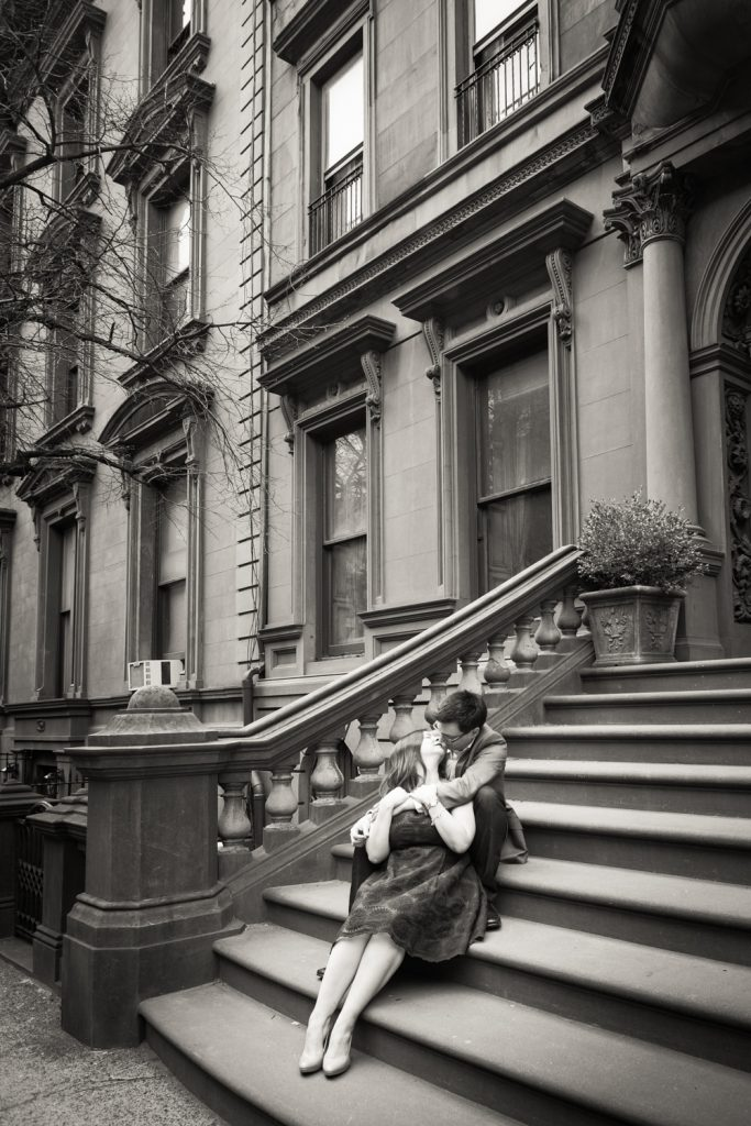 Black and white photo of couple kissing on steps of brownstone