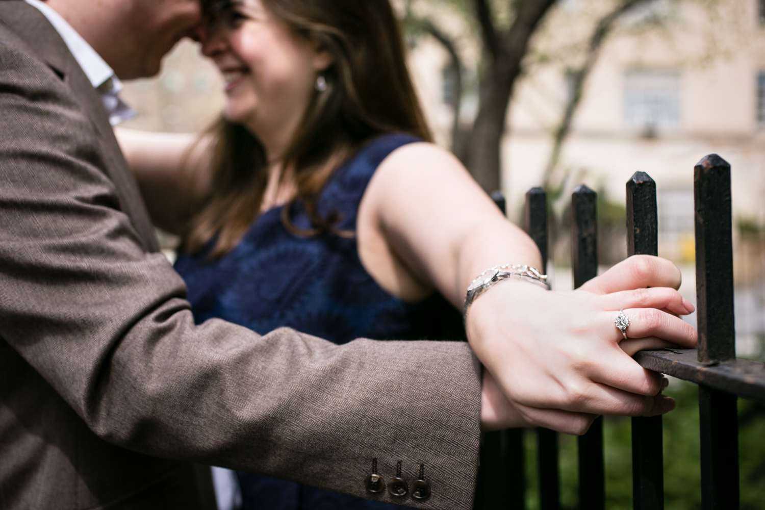 Close up on couple holding hands against fence railing