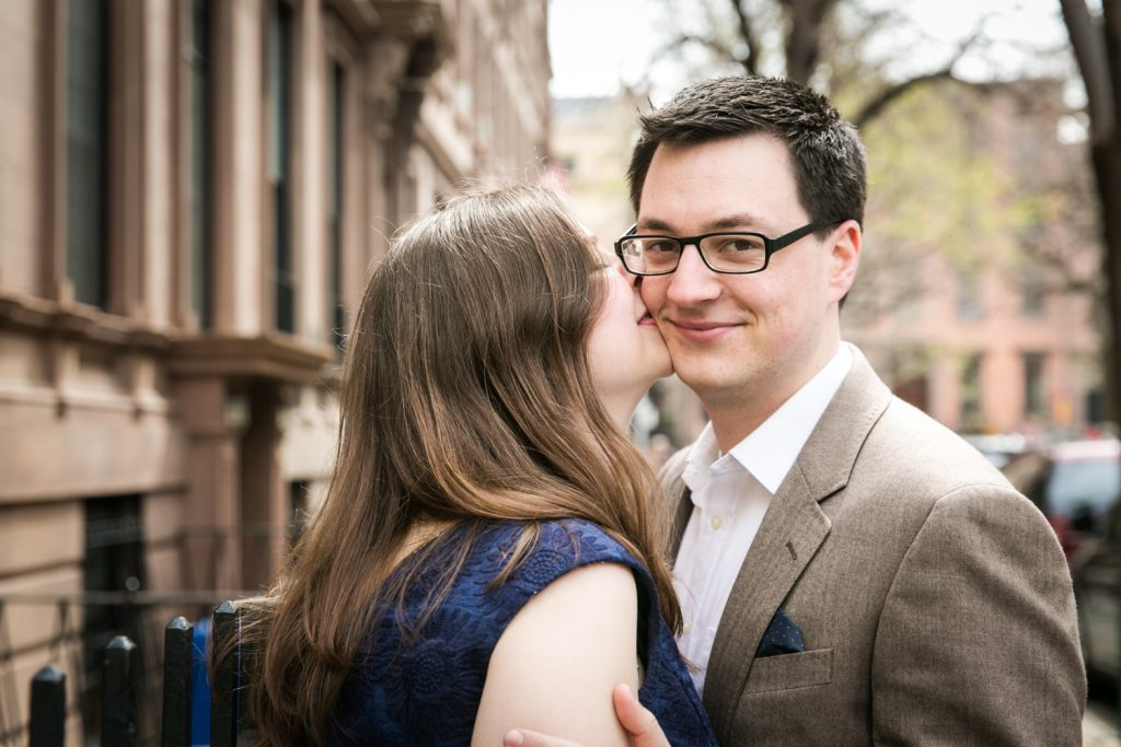 Woman kissing man wearing glasses on the cheek