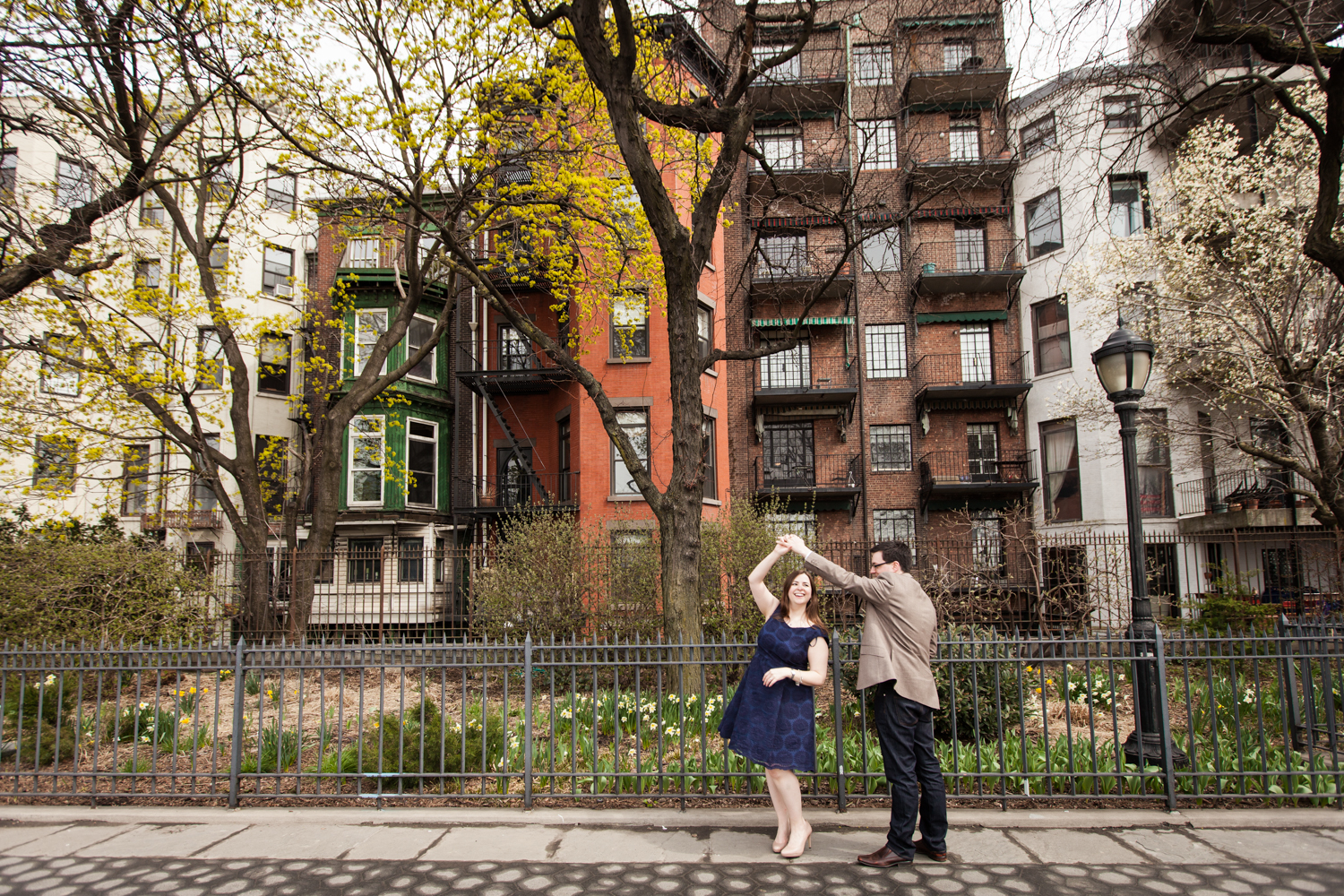 Brooklyn Promenade engagement photos of couple dancing in front of apartment building