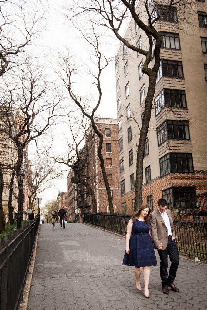 Couple holding hands and walking on sidewalk in Brooklyn Heights