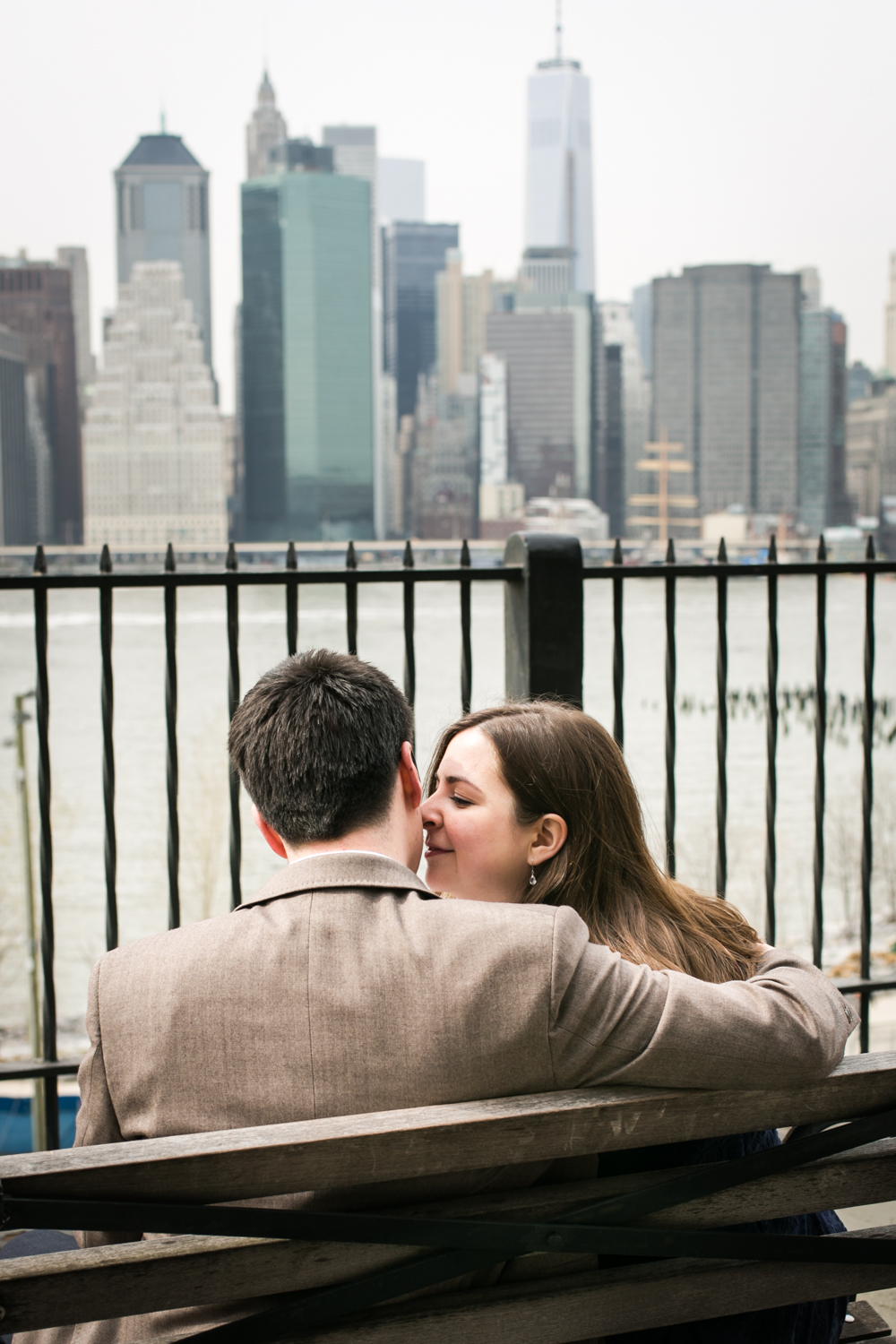 Couple sitting on bench on Brooklyn Promenade and woman kissing man on cheek
