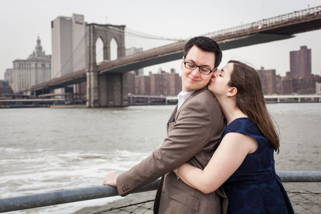 Brooklyn Promenade engagement photos of woman hugging man from behind with Brooklyn Bridge in background
