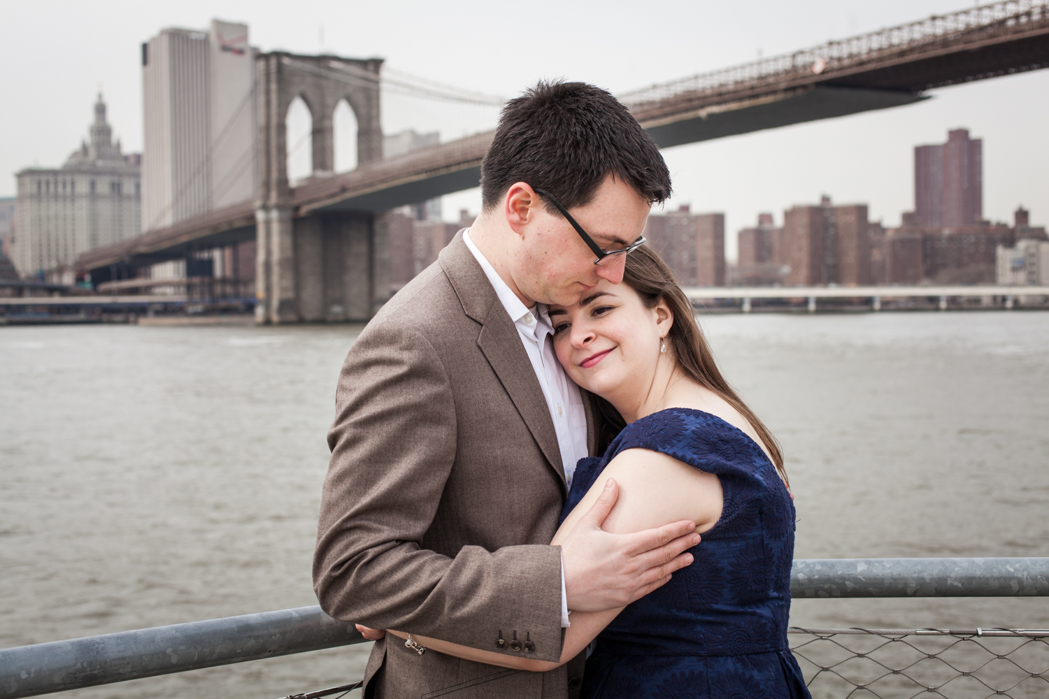 Brooklyn Promenade engagement photos of couple hugging Brooklyn Bridge in background