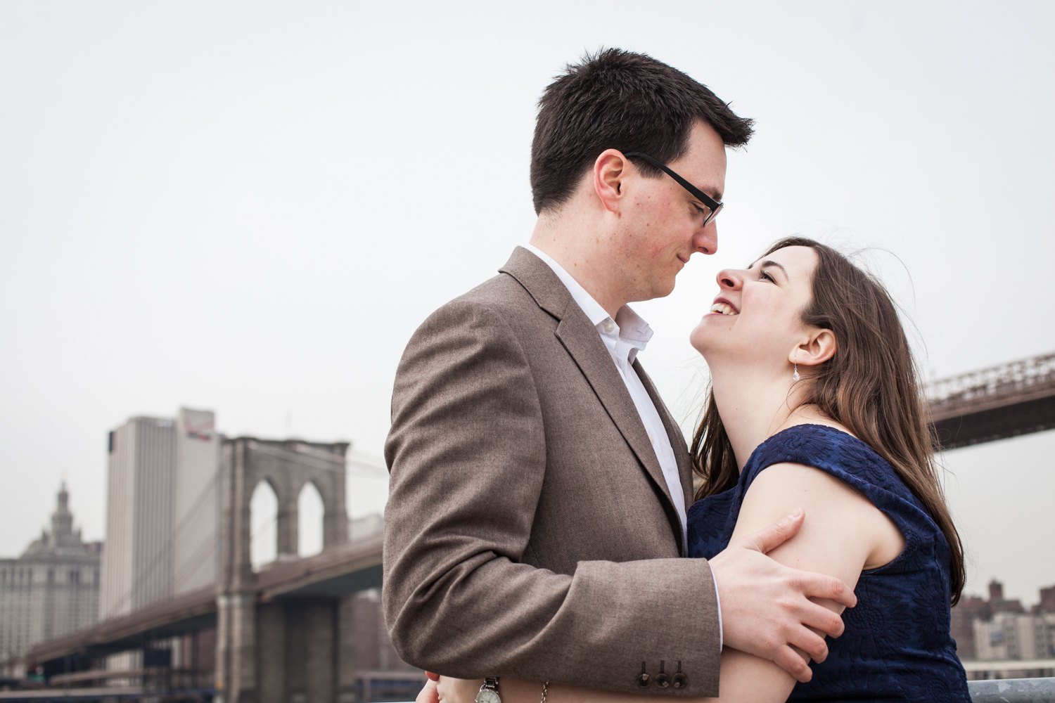 Brooklyn Promenade engagement photos of couple hugging with Brooklyn Bridge in background