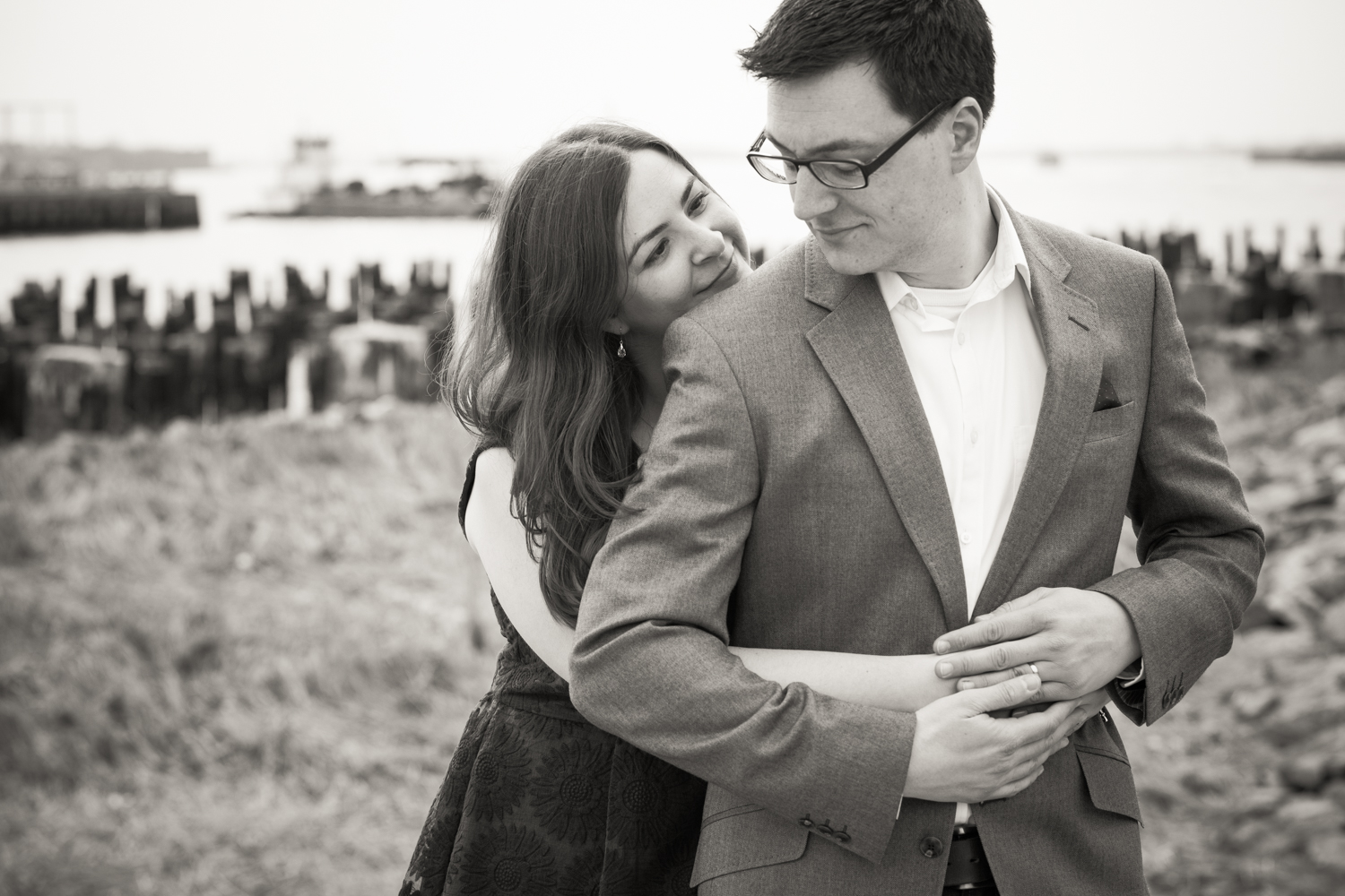 Black and white photo of couple hugging with abandoned dock in background