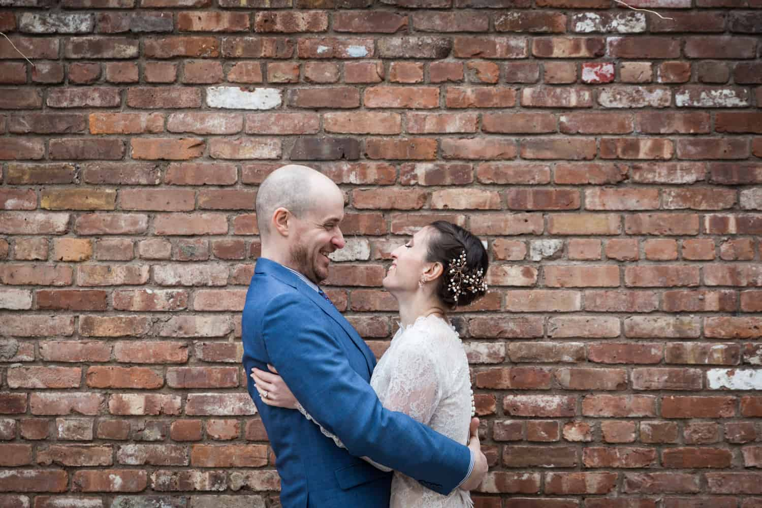 Bride and groom hugging in front of brick wall for an article on what is wedding photojournalism