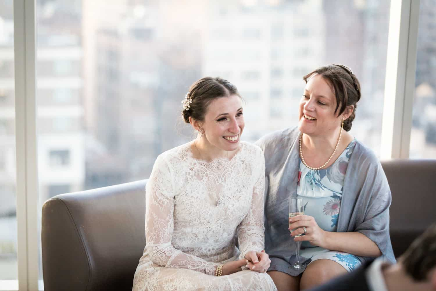 Bride and bridesmaid chatting on couch for an article on what is wedding photojournalism
