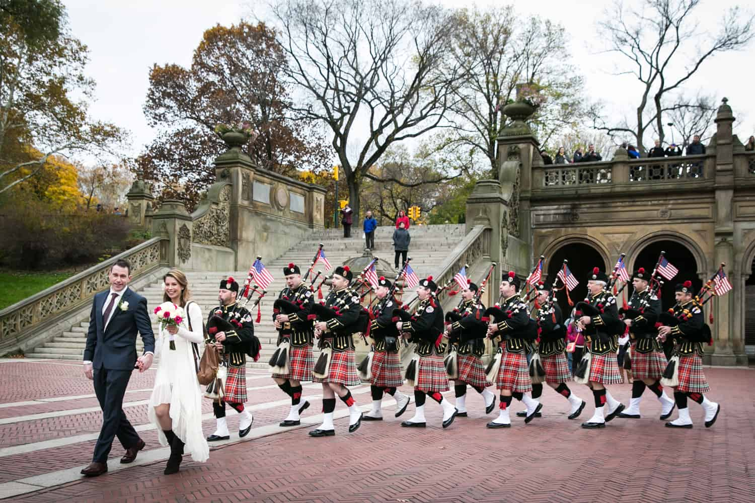 Bride and groom in front of Scottish marching band at a Bethesda Fountain wedding in Central Park