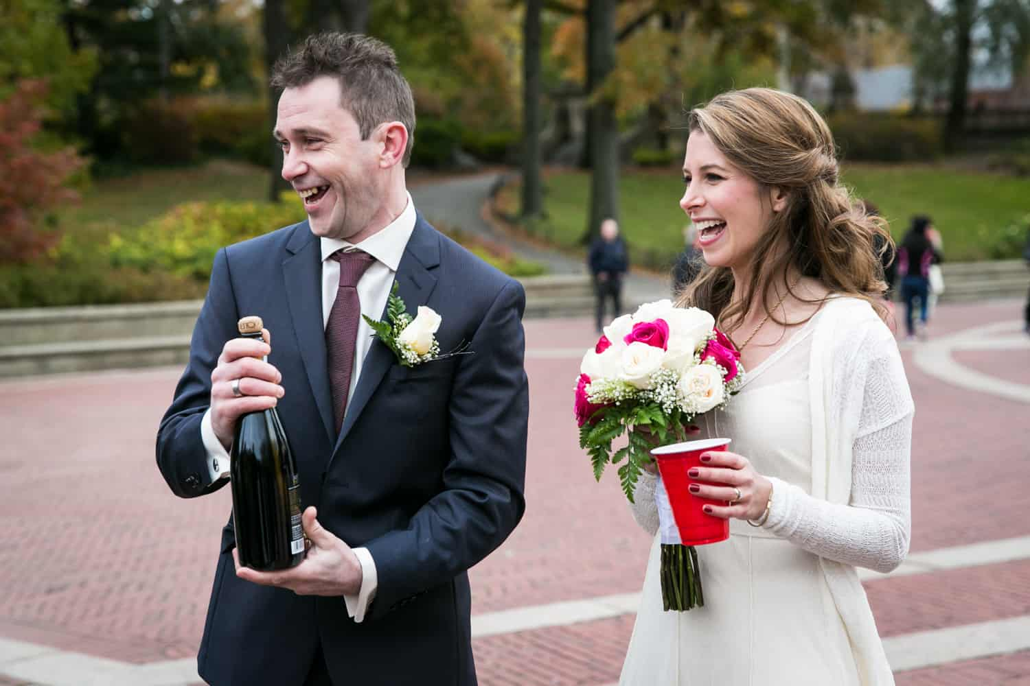 Bride with groom holding champagne bottle at a Bethesda Fountain wedding in Central Park
