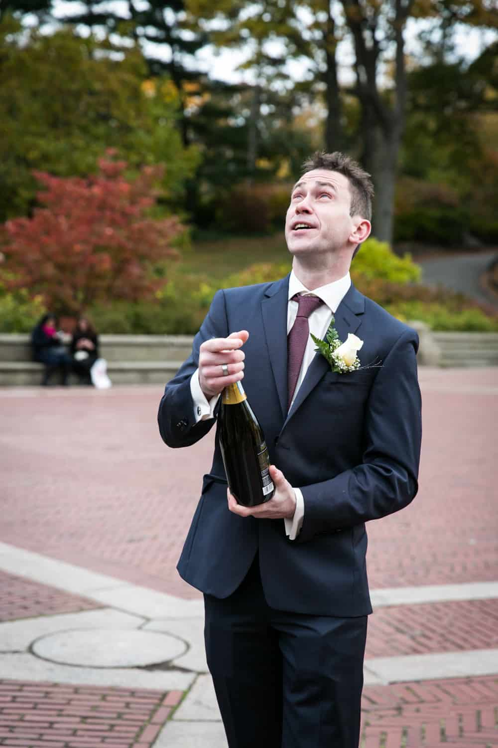 Groom opening champagne bottle at a Bethesda Fountain wedding in Central Park