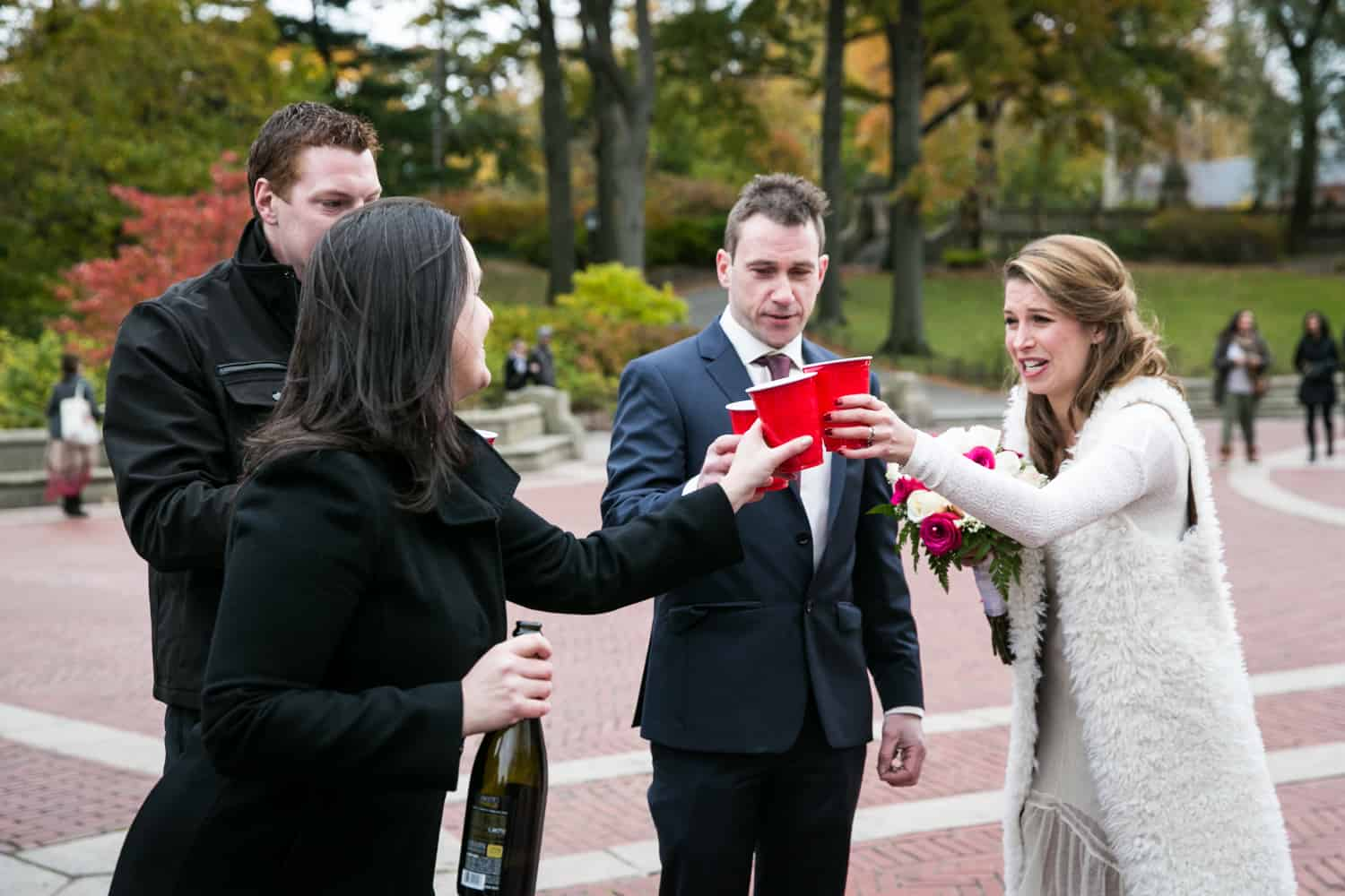 Bride, groom, and guests toasting with red plastic cups