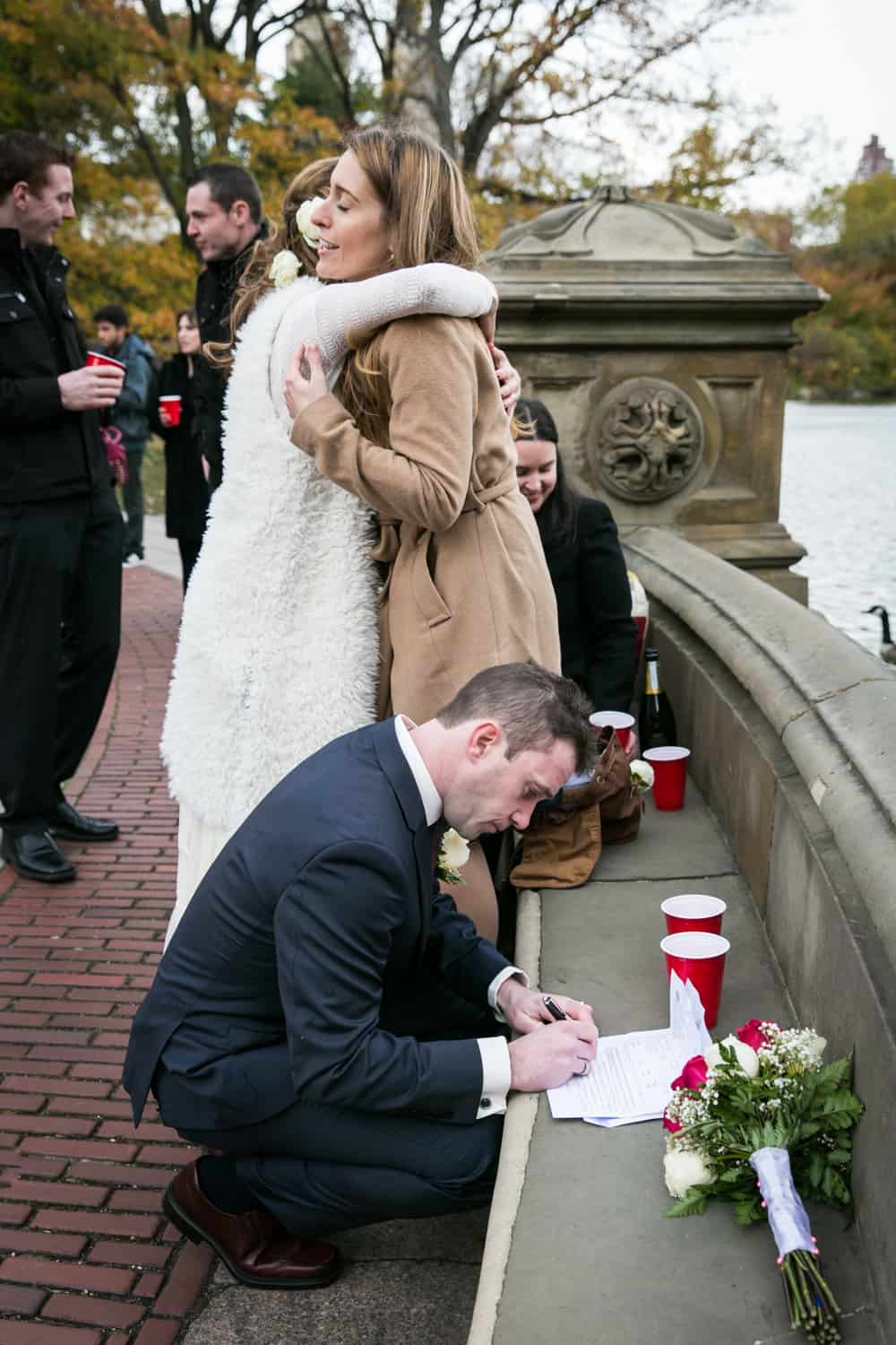 Bride hugging guest and groom signing marriage license on stone seat