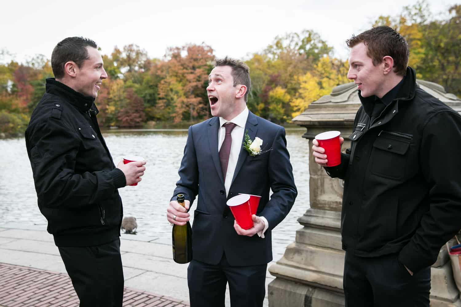 Groom celebrating with two male guests at a Bethesda Fountain wedding in Central Park
