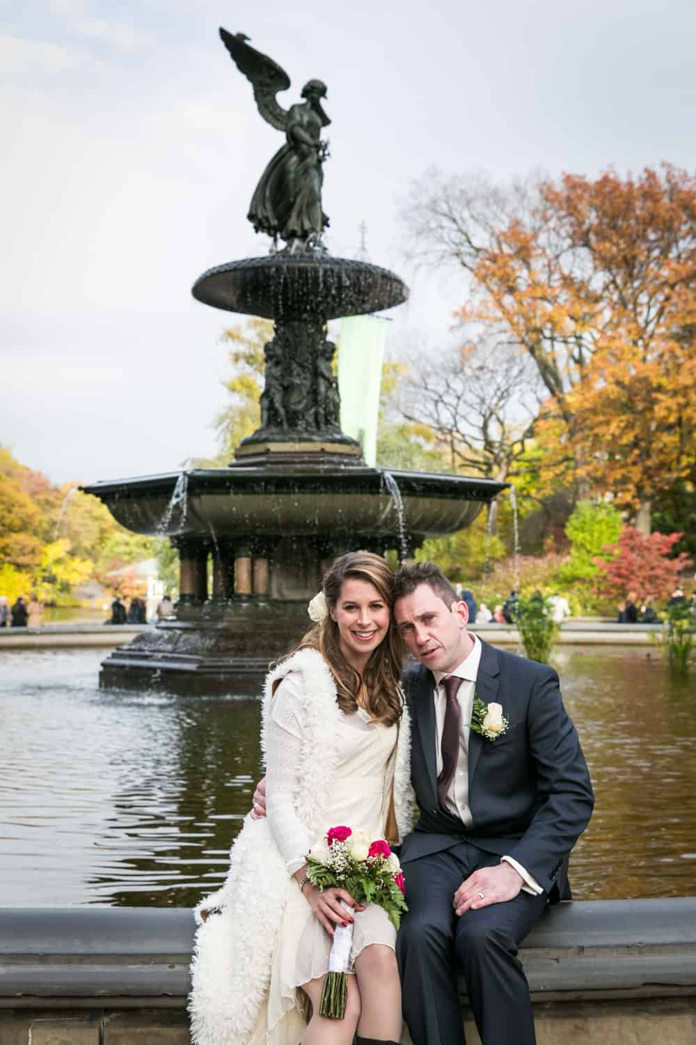 Bride and groom sitting in front of Bethesda Fountain