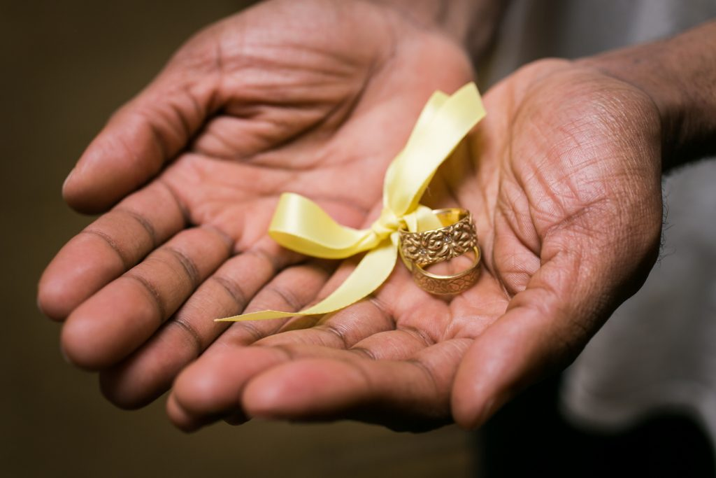 Close up of African American hands holding a set of wedding rings with yellow ribbon