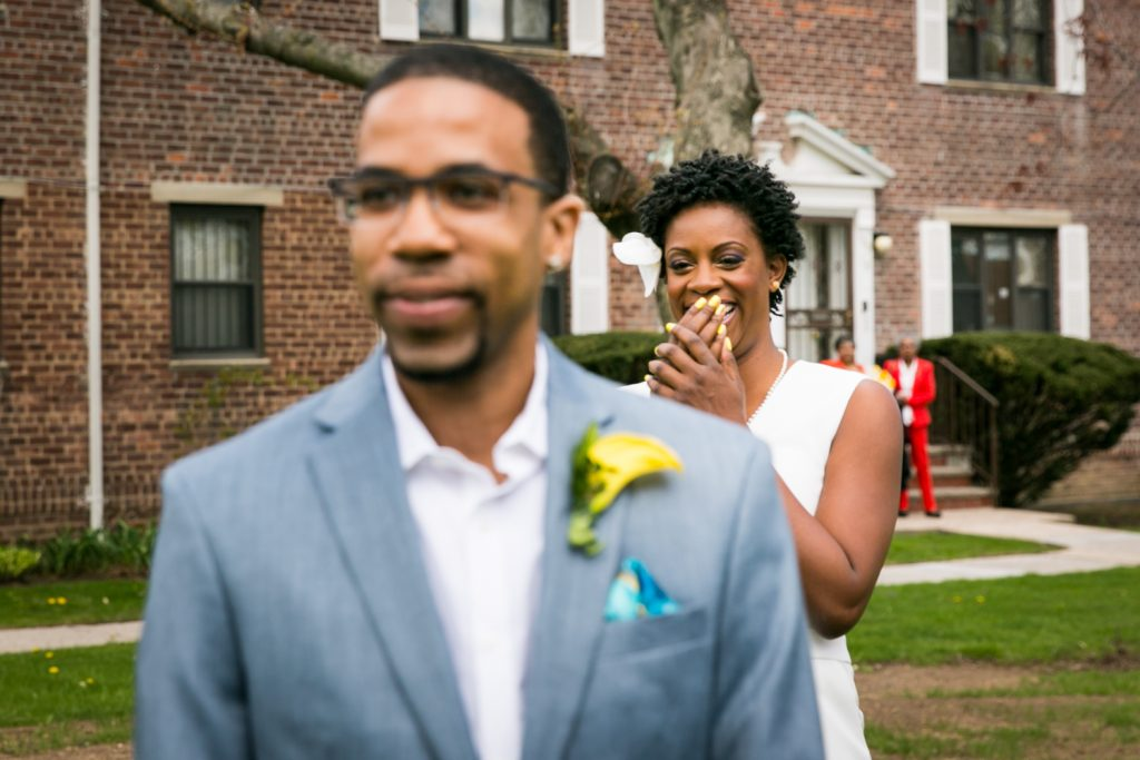 Bride laughing behind groom's back at a Flushing Meadows Corona Park wedding