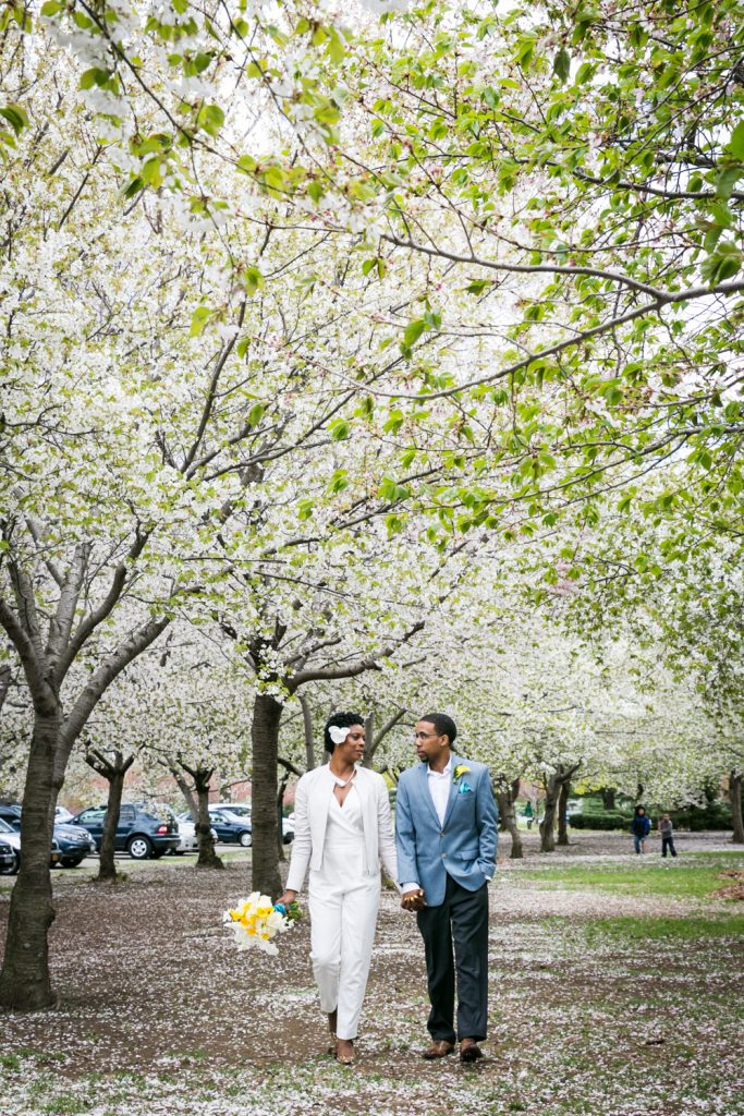 Bride and groom walking under cherry blossom trees in Flushing Meadows Corona Park