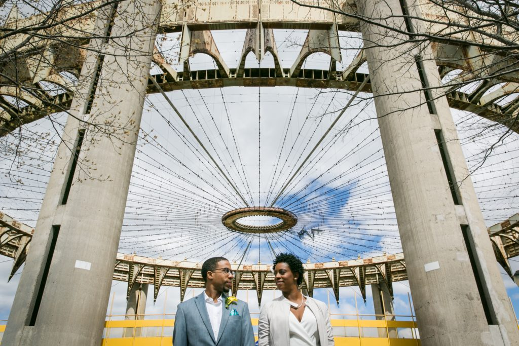 Portrait of bride and groom under world's fair architecture in Flushing Meadows Corona Park