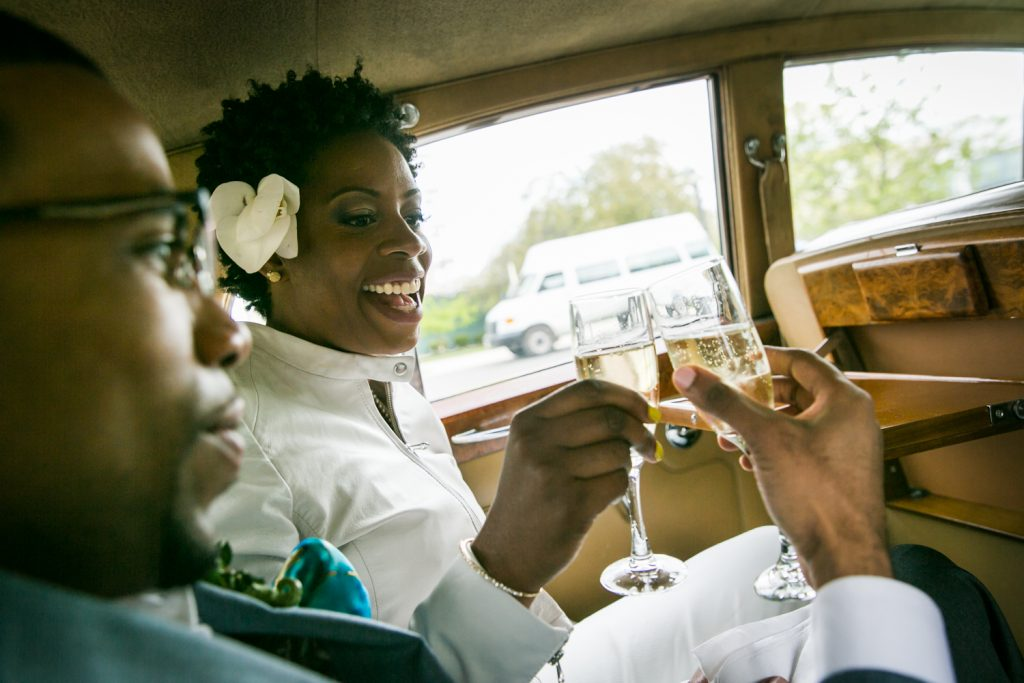 Bride and groom toasting with champagne in the back seat of a car