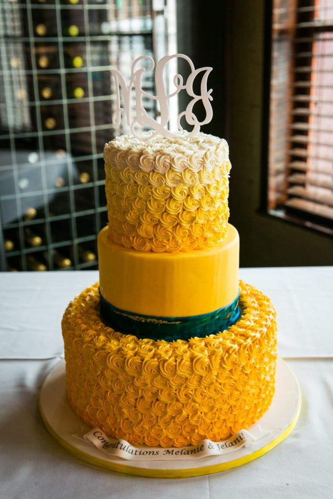 Yellow-frosted wedding cake at a Flushing Meadows Corona Park wedding