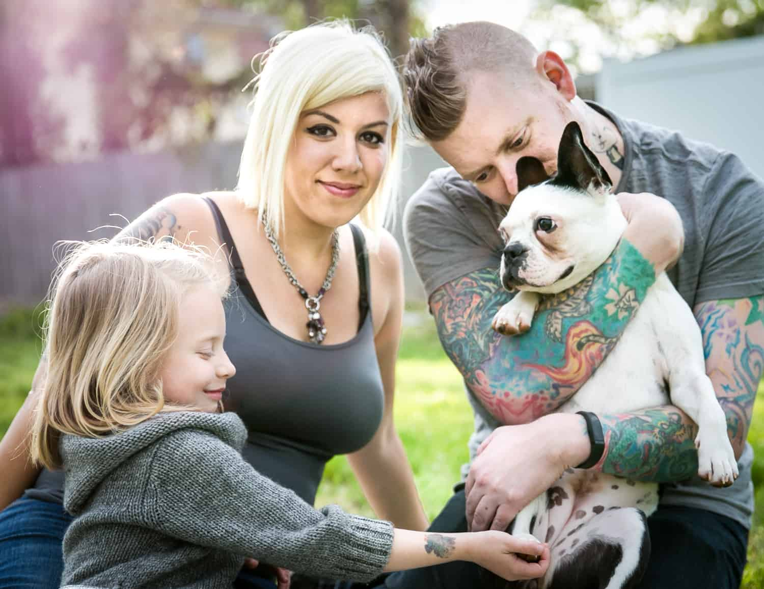 Pregnant woman, man, young girl and dog in backyard