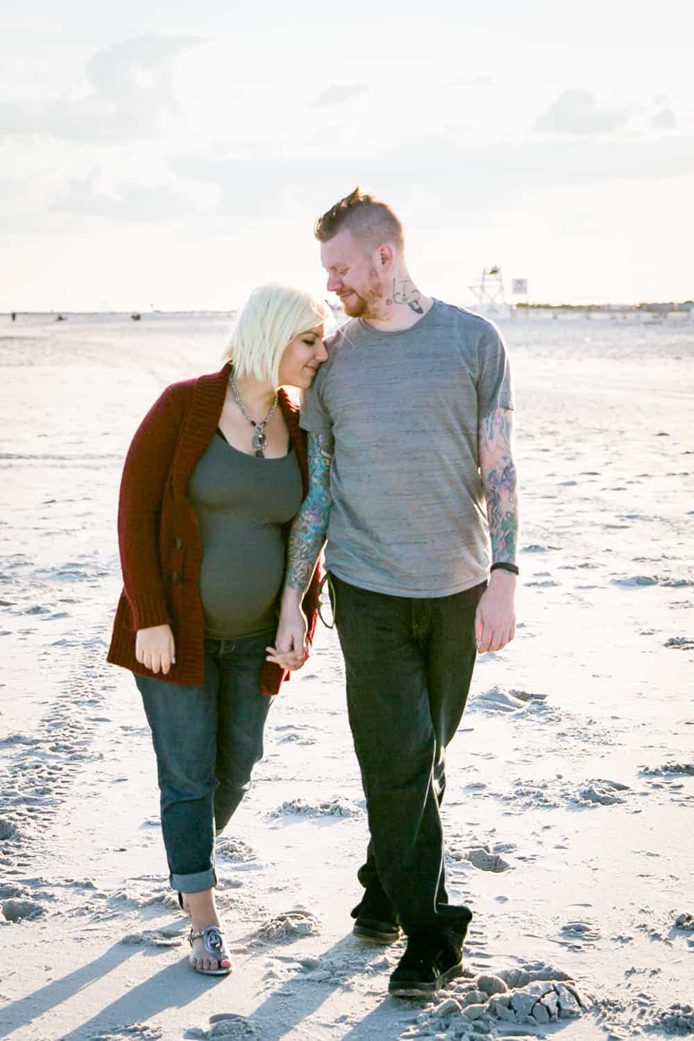 Pregnant blond woman and partner on beach for an article on how to prepare for a maternity photo shoot