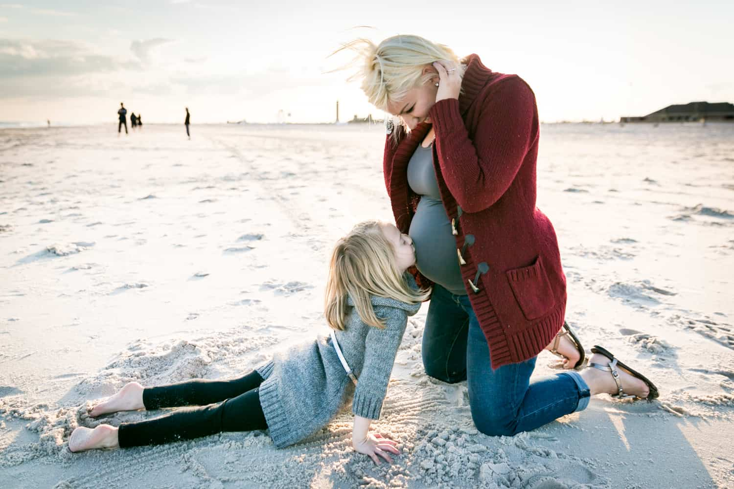 Little girl kissing blond pregnant woman's stomach