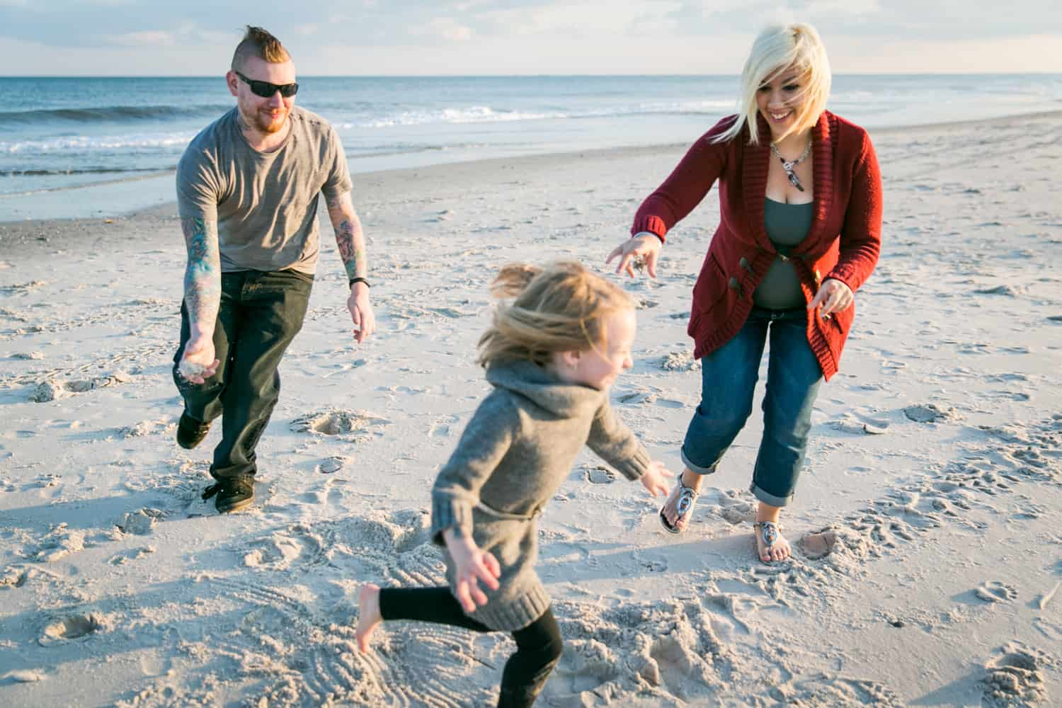Father and mother chasing little girl on beach