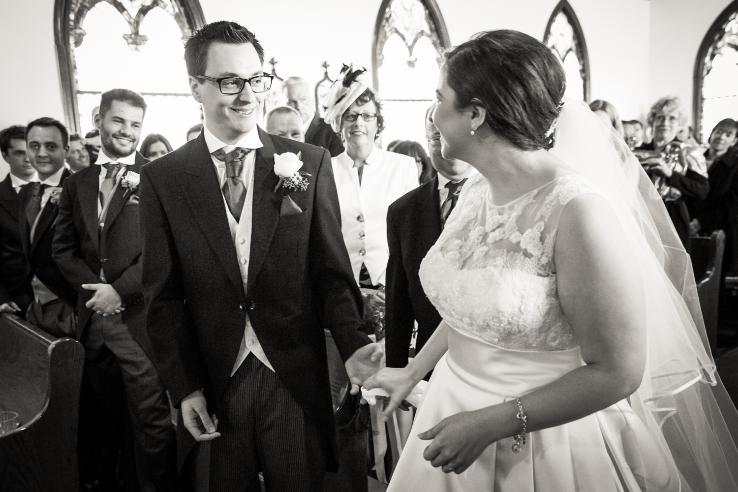 Black and white photo of bride and groom seeing each other for the first time in front of altar