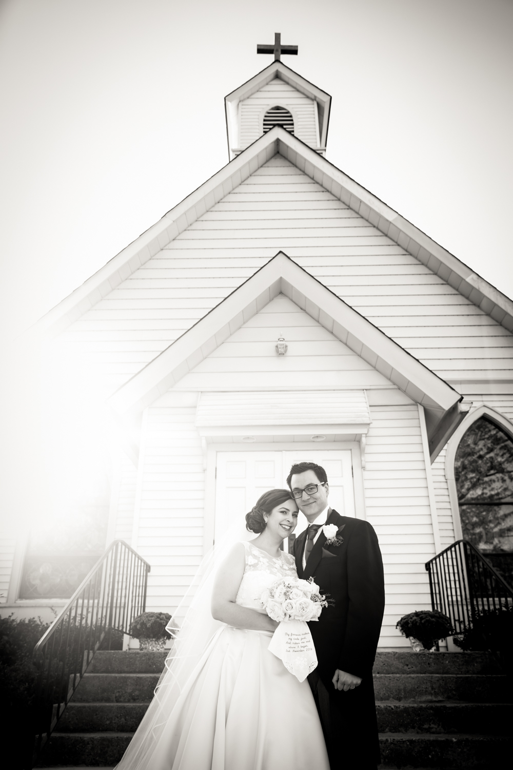 Black and white photo of bride and groom outside St. James Church in Pennington, NJ