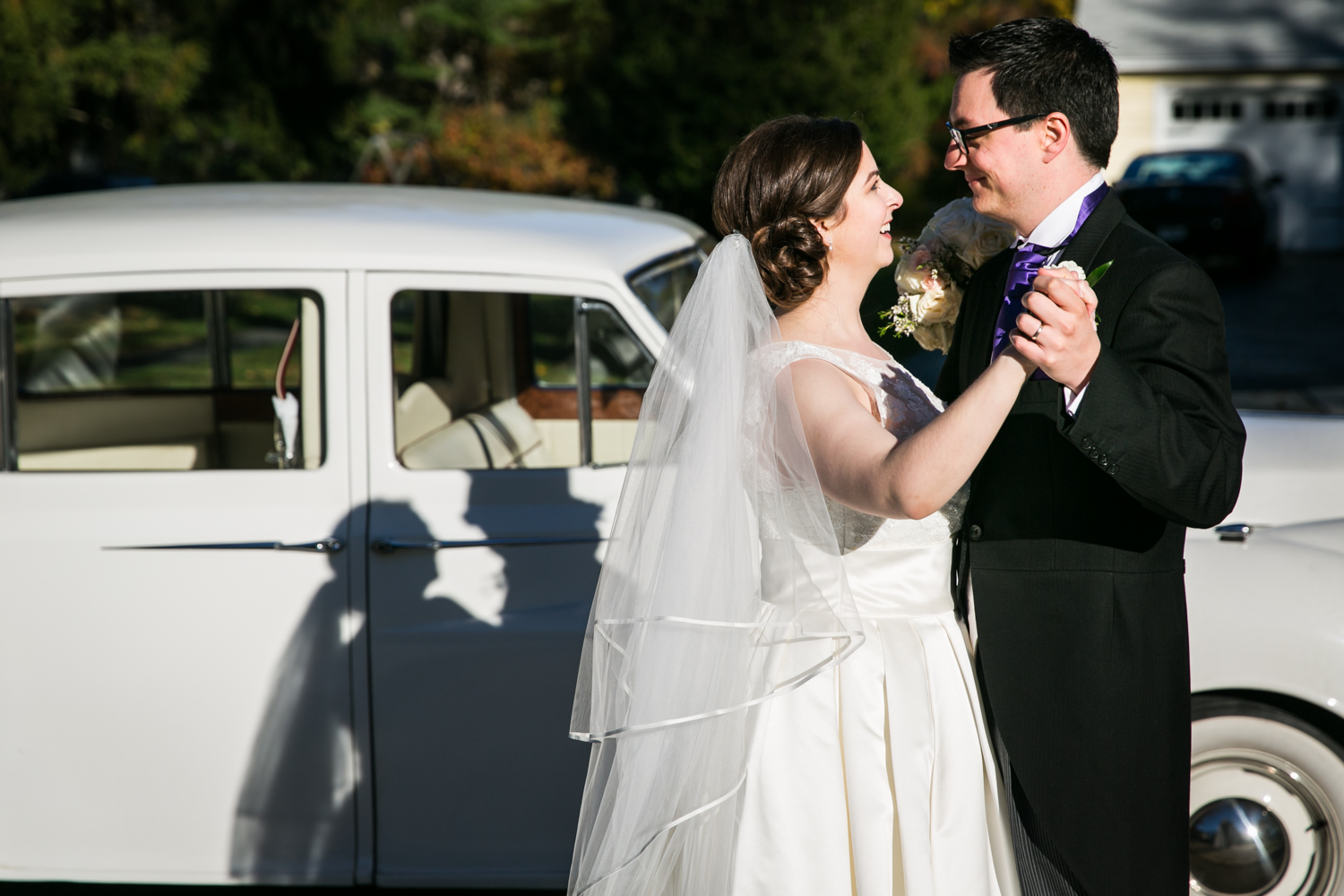 Bride and groom dancing in front of white Rolls Royce