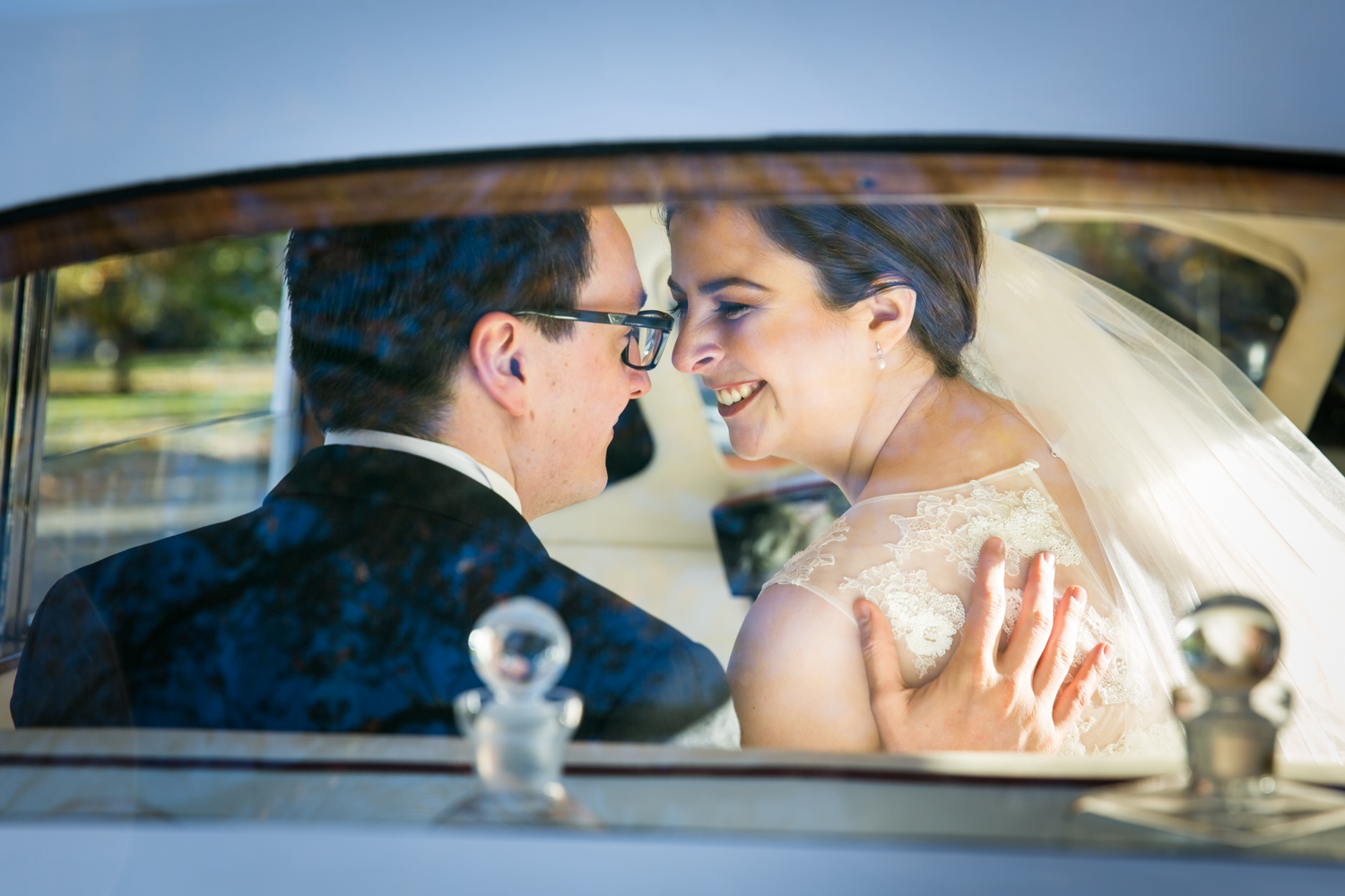 View of bride and groom in back seat of Rolls Royce