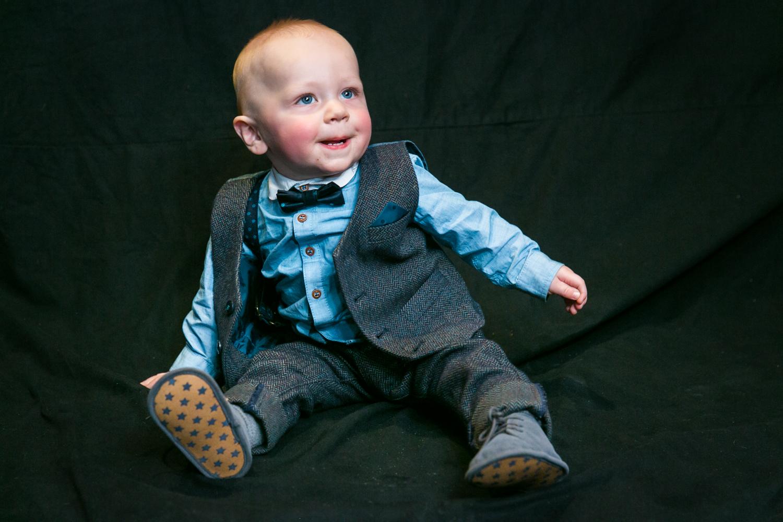 Baby boy sitting on black cloth