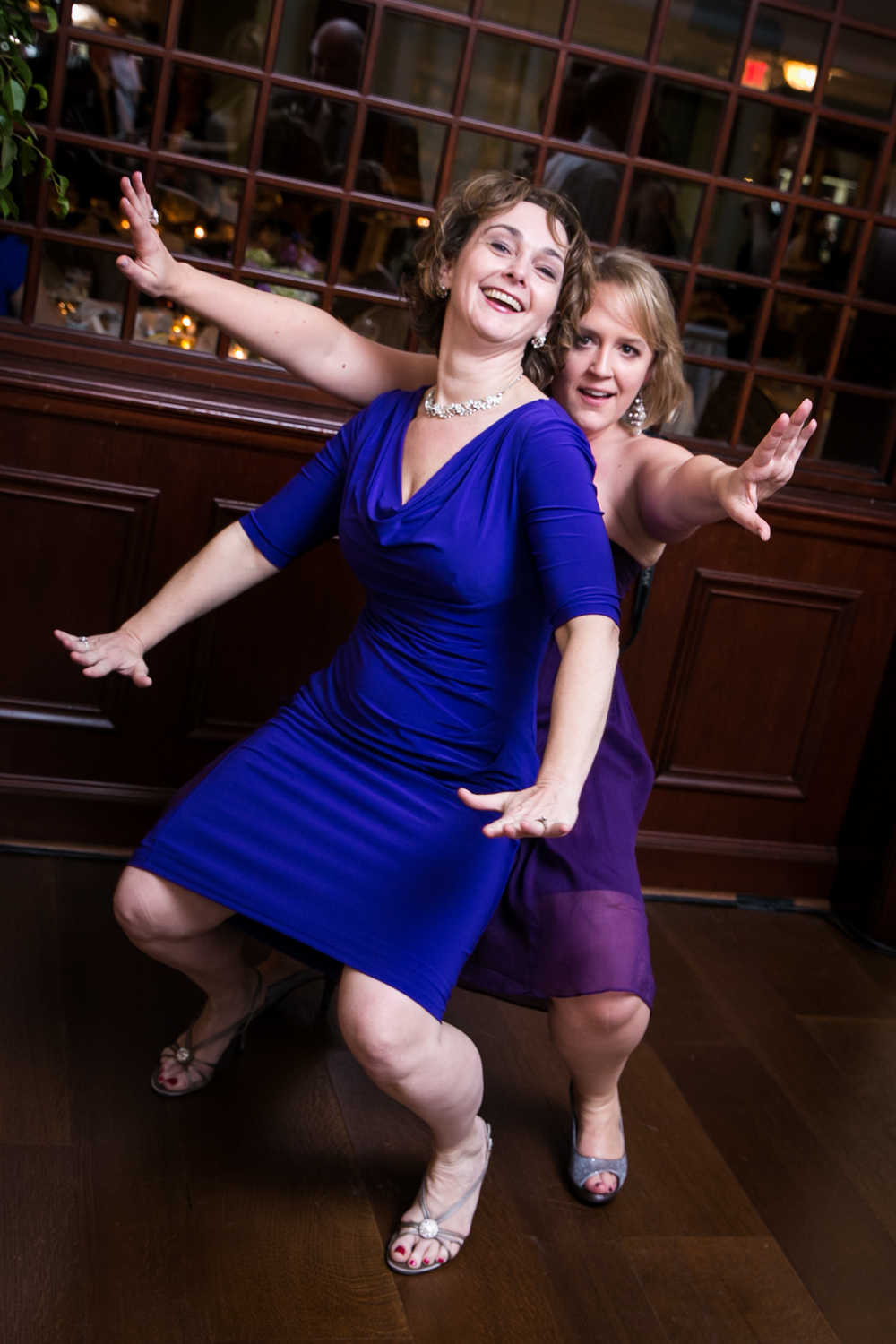 Two female guests dancing with arms outstretched at a Nassau Inn wedding