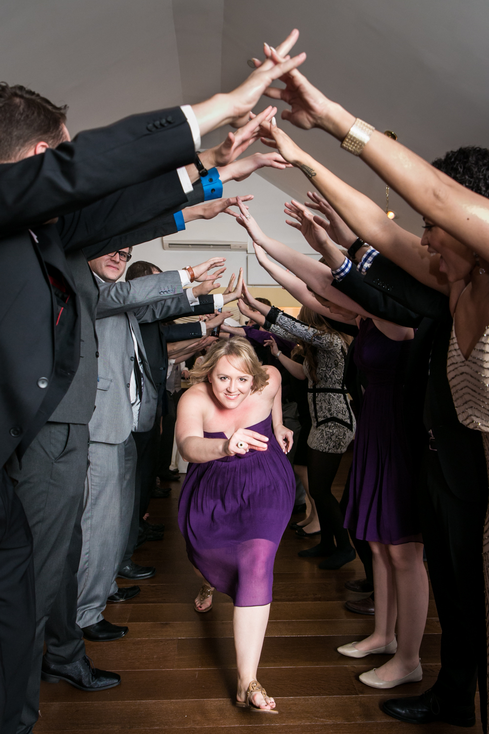 Female guest wearing purple dress running under arch of other guests' arms