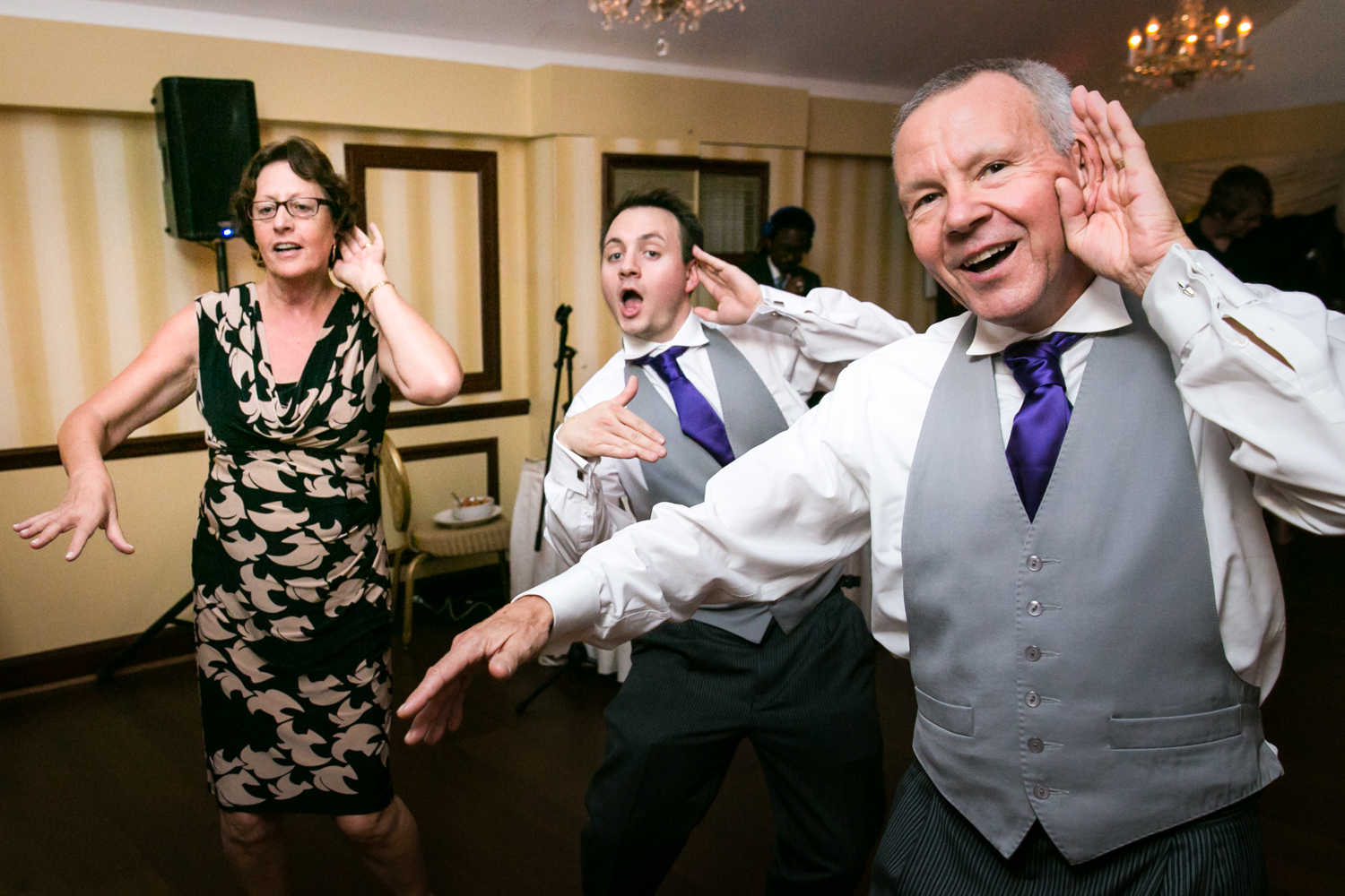 Three guests dancing at wedding reception with arms outstretched