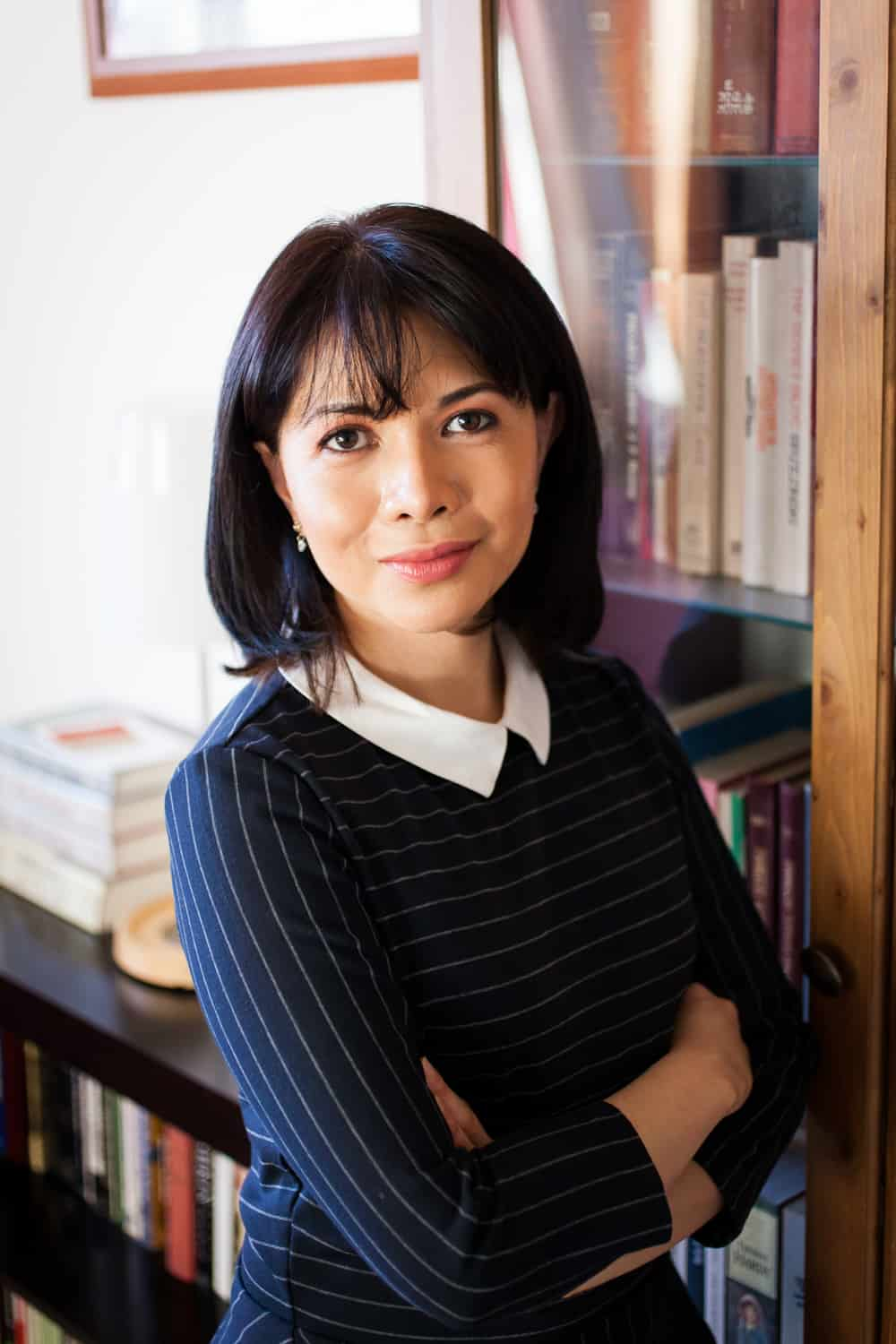 Woman leaning against bookshelf wearing pinstripe blouse for an article on online portrait tips